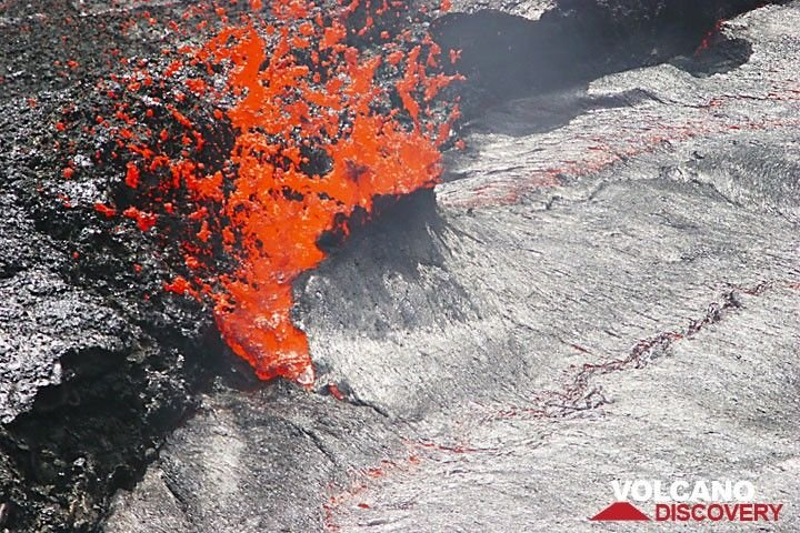 An exploding bubble of gas disrupts the crust of the lava lake. (Photo: Tom Pfeiffer)