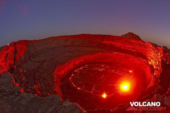 The red glow of the lava illuminates the crater walls under the blue sky of dusk. A small group of observers is on the left crater rim. (Photo: Tom Pfeiffer)