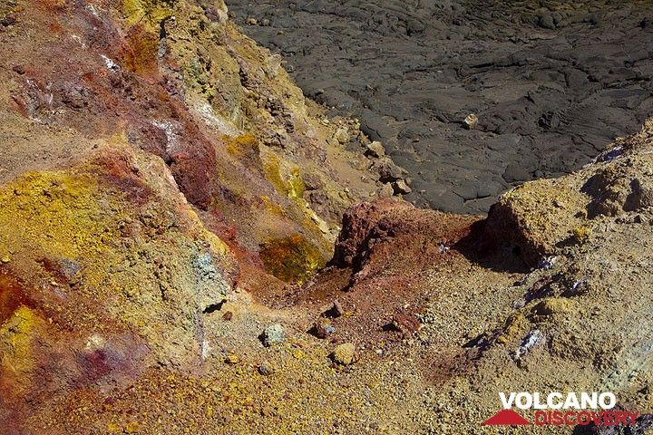 Colorful red and yellow oxides stain the ground on the outer crater rim of the caldera in an area with wet fumaroles. (Photo: Tom Pfeiffer)
