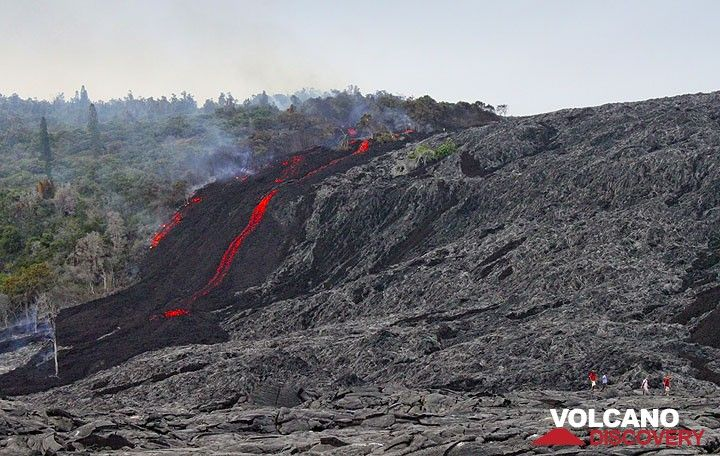 A tour group departs the leading edge of an 'a'a lava flow at the base of Pulama Pali, being fed from the Peace Day Fissure on Pu'u 'O'o vent on K?lauea volcano on December 4, 2011. (Photo: Philip Ong)