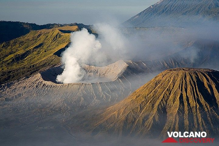 Smoking Bromo volcano and Batok cone with its deep radial erosion gullies (c)