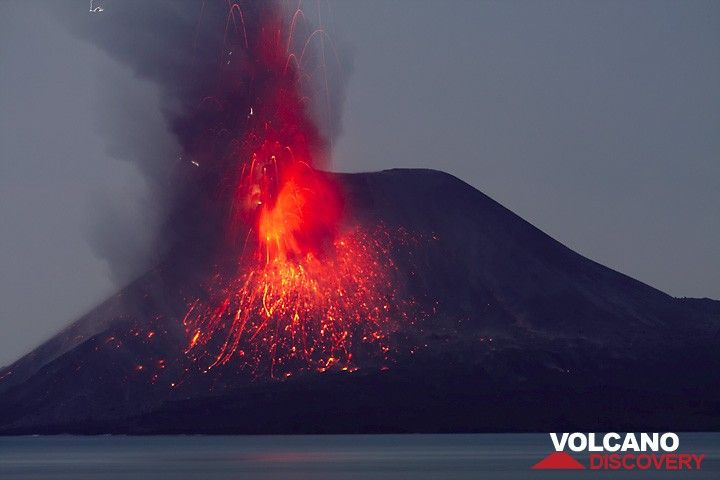 An eruption showers the s flank of the summit cone with incandescent cinders. Small lightning discharges in the eruption plume. (c)