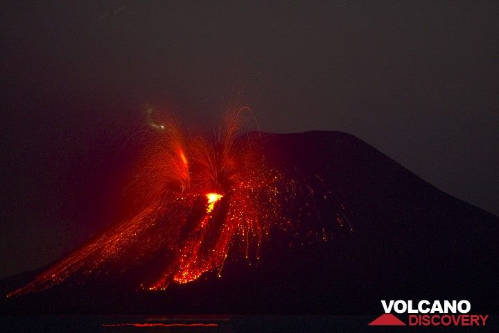 Powerful eruption with lightning during the night. Incandescent ash and cinders form a small flow on the cone's flank.  (c)