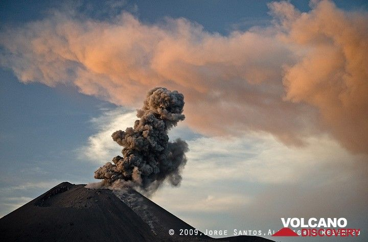 The ash cloud from the previous eruption is illuminated by the setting sun while the crater erupts a weak plume of ash. (Photo: Jorge Santos)