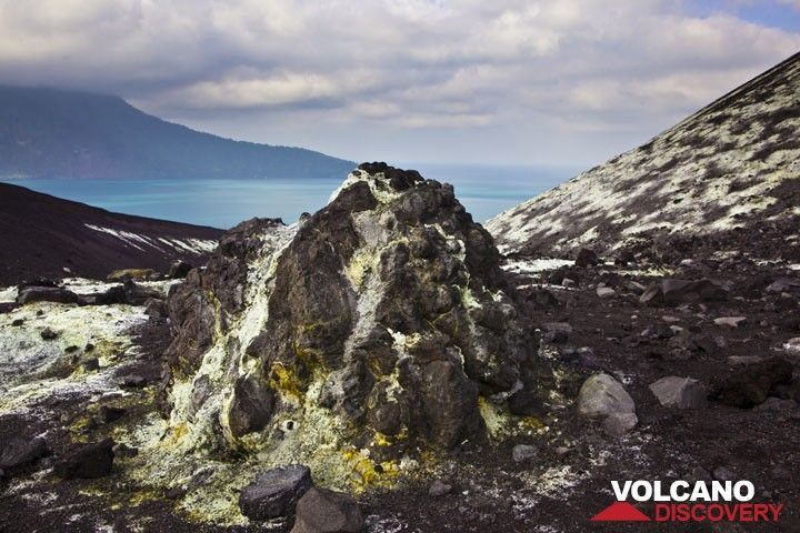 A large bomb in the saddle between the old crater rim and the main cone of Anak has been covered by white and yellow sulfate deposits. (Photo: Tom Pfeiffer)