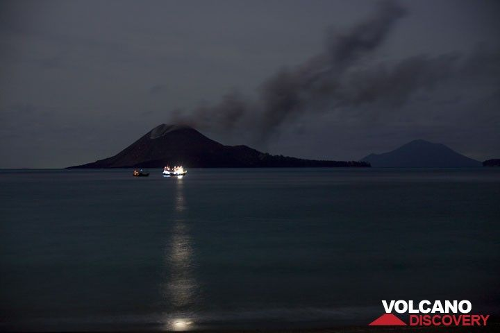 Two fishing boats in front of the volcano. (c)