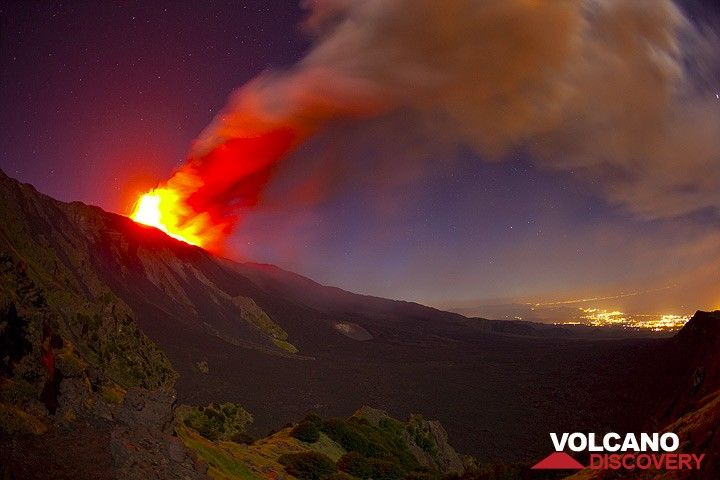View over the Valle del Bove with the lava fountain and the ash plume from the eruption, drifting east by strong westerly winds towards Giarre, whose lights are in the background. (Photo: Tom Pfeiffer)