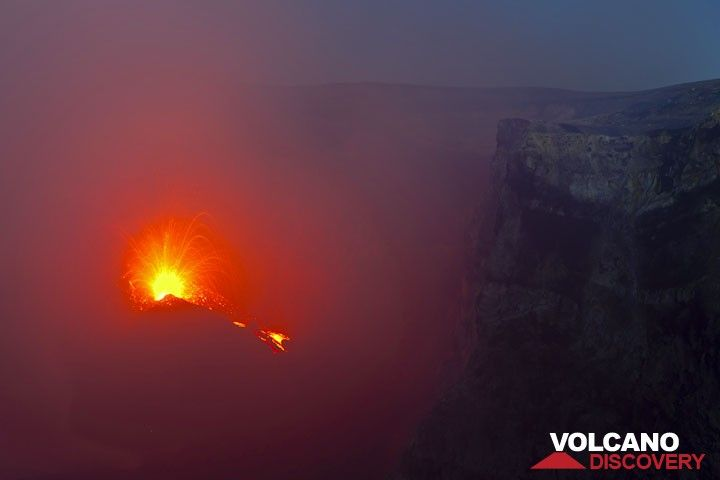 Near-continuous strong spattering and effusion of a small lava flow from the new intra-crater cone illuminate the Bocca Nuova crater of Etna (3 Aug 2012). (Photo: Tom Pfeiffer)