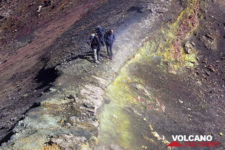 Group on a narrow ledge that separates two vents on Etna volcano, Italy. (Photo: Tom Pfeiffer)