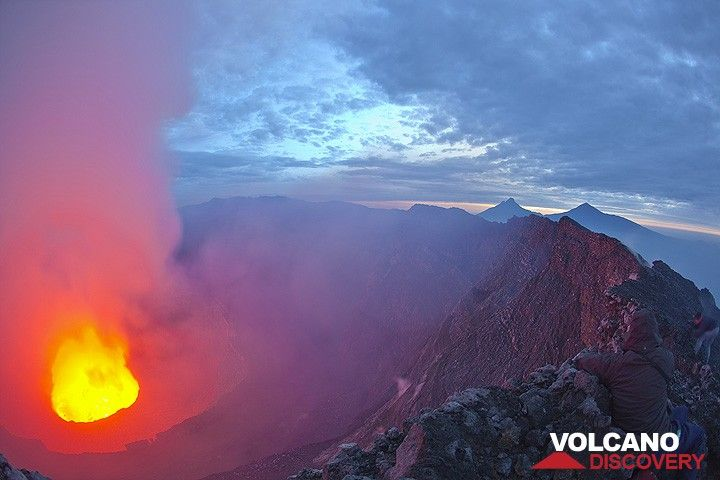 Morning comes fast! A last photo of the lava lake in its giant crater, before fumes become too dense. Jean Michel, at the lower right, merges with the ground. Mikeno and Karisimbi in the background. (Photo: Tom Pfeiffer)