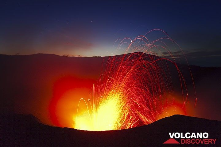 A stronger eruption after sunset sends glowing bombs into the sky, hitting the moon. (Photo: Tom Pfeiffer)