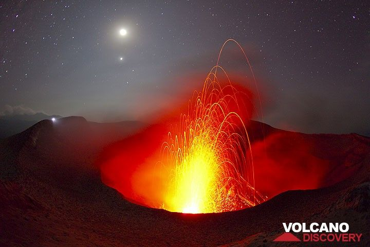 The erupting crater of Yasur volcano under a moon- and starlit sky. The torch of a distant observer on the opposite rim looks like a second moon. (Photo: Tom Pfeiffer)