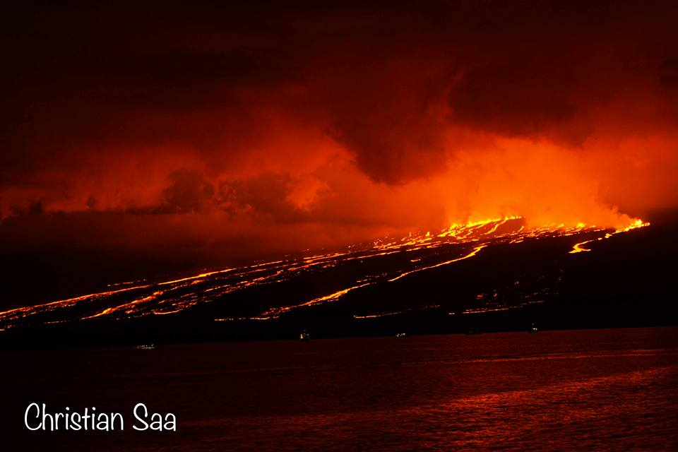 The nighttime sky is turned red due to the red glow from the lava fountaining from the fissures, forming multiple rivers flowing towards the ocean (image shared on Facebook page of Christian Saá)