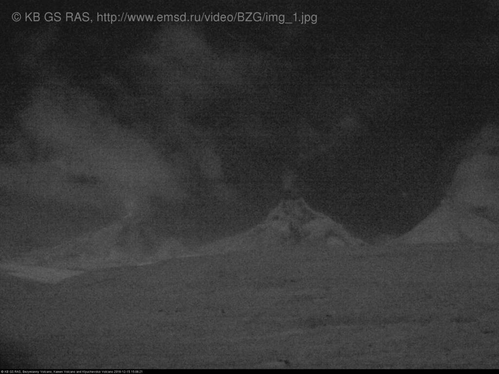 Bezymianny volcano (left) with a faint glow and significant steaming