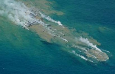 Press photos distributed by the Japanese Coast Guard, showing the site of a probable undersea eruption of Futuku-okanoba submarine volcano on 3 July 2005. Note the discoloration of the sea-water, as well as floating peices of steaming lava blocks on the surface.