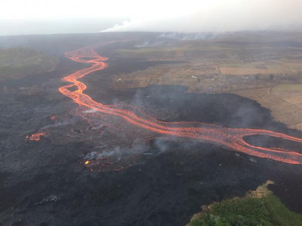 The fissure 8 channel continues to carry lava toward the coast on the west side of Kapoho Crater (vegetated cone, far left). Northwest of this cone, overflows (lower left) of the channel occurred overnight, but lava was confined to the existing flow field and did not threaten any homes or structures. (image 23 July: HVO / USGS)